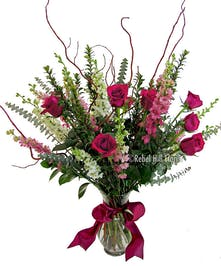 Vase of lovely roses with two accent flowers and assorted foliage