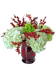 Red hurricane vase featuring hydrangea and seasonal red