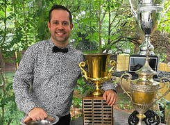 A member of our team poses in our garden, alongside various trophies and awards